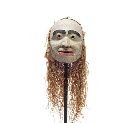 Forest spirit mask, humanoid features, mostly white face with red lips and prominent black eyebrows, cloth and cedar drape on back.