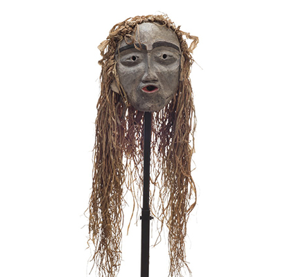 A small forest spirit mask, mostly white face, pursed red lips, prominent black eyebrows, long cedar trim draping from top and back.