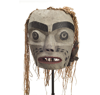 A large forest spirit mask, mostly white, red lips, large open mouth, some cedar trim on back and sides. Eyes are painted. Mask has no eyeholes.
