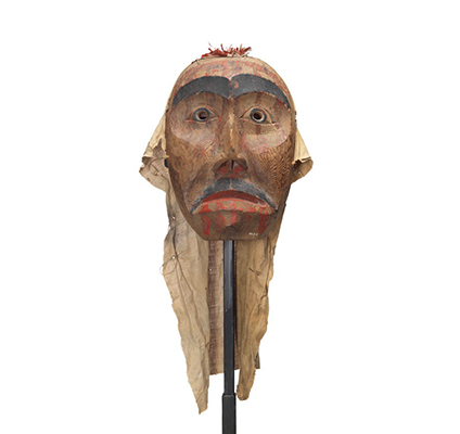 A mourning mask red cedar with painted black eyebrows pupils and moustache. Red paint drips on the forehead, below eyes and lips.