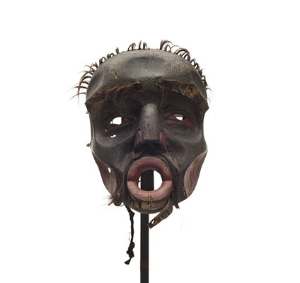 A Dzunuk´wa or wild woman of the woods mask, black stained wood with dark red on nose and cheeks, eyes and nostrils, short tufts of hair on scalp, worn fur patches.