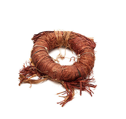 A torus shaped headdress of red cedar bark, formed by wrapping bark around wool loop, bundle of cedar front and two cedar tassels on back side.