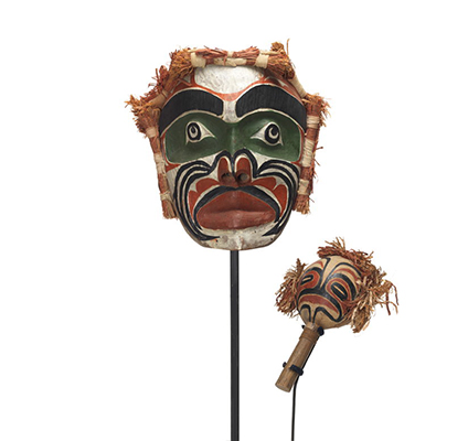 A Yadan or large rattle and Imas or Ancestor Mask painted in black, green, red and white with cedar bundles on top and sides.