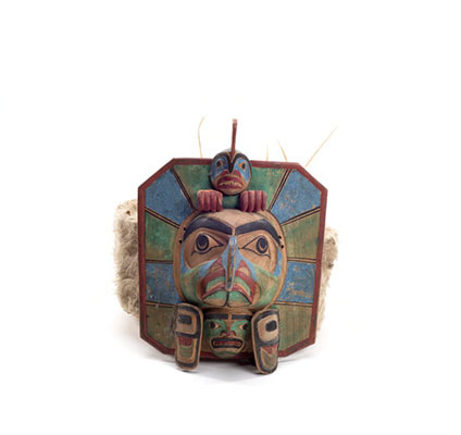 Yaxwiwe' frontlet, carved wood hexagonal shape with blue and green sections, central bird face with whale figure above, ermine and sea lion whisker trim.