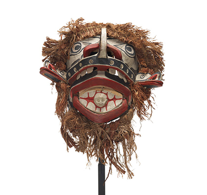 A large and monstrous Baxwbakwalanuksiwe' mask, surrounded by cedar trim with two mouths, two protruding beak figures and skull figure in mouth.