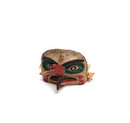 A 'Na'nalalał or weather mask, long red proboscis over a curved beak painted black with red edges, green patches around eyes, cloth head band.