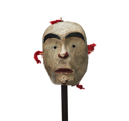 A white-faced mask, small circular eyeholes, red paint on lips and surrounding nostrils, bright red fabric rigging.