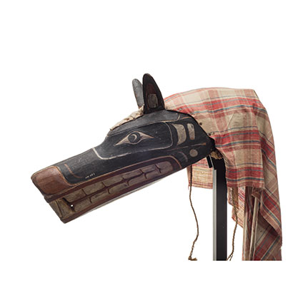 Xisiwe' or wolf mask, one of several with long snout and large teeth, painted red and black with plaid cotton head cover, prominent upright ears.