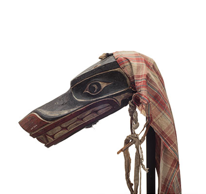 Xisiwe' or wolf mask, one of several with long snout and large teeth, painted red and black with fragment of plain cotton head cover.