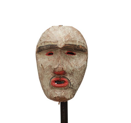 A white-faced mask, patches of red around squinting eyeholes, nostrils and lips, think moustache, heavy brow.