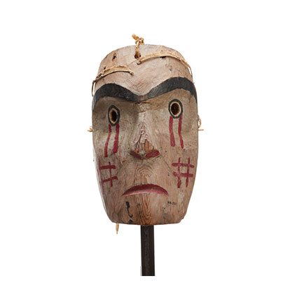 Kwasanuma or mourning mask, cedar with red drips of paint below eyes, cross-hatch pattern in red on cheeks, mournful expression.