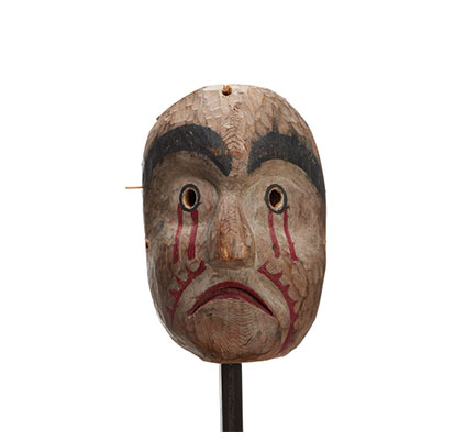 Kwasanuma mourning mask, carved of cedar with black eyebrows, round eyeholes, paint dripping from eyes and cheeks, mournful expression.