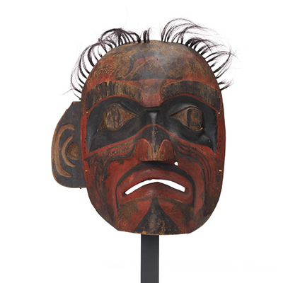 Large deaf man mask, lacks eyeholes, tufts of horsehair above, black bands of paint around eyes, mostly red and black markings on face, sad expression.