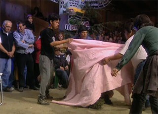 A potlatch scene where Wildman of the woods is hiding behind a pink blanket surrounded by four men.