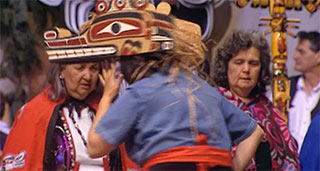A dancer wearing a wooden hat-like mask appears with her back to the camera, two other women in red capes face the camera.