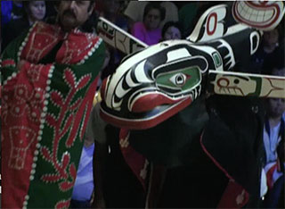 A red and green button blanket appears to the left of a brightly painted whale mask with pectoral fins open.