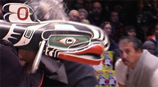 Dance assistants surround a whale mask, eagle down resembling water is blown from a spout into the air.