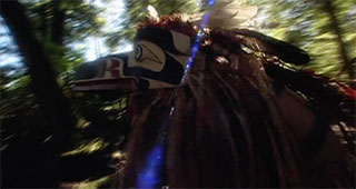 A masked dancer in ceremonial regalia moves quickly through a shaded forest.