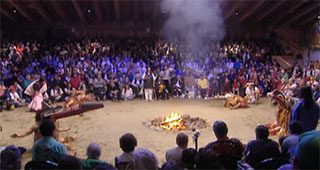 Smoke rises above a burning fire pit in the big house. Around the fire a group of dancers and behind them the audience.