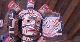 A dancer wears a brightly decorated and detailed transformation mask in the open position.