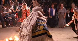 Three dancers in ceremonial regalia move around a fire at a potlatch in the big house.