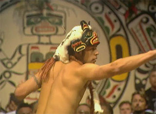 Shirtless man wearing a headdress-style mask stands in profile before a dance curtain and points to the right.