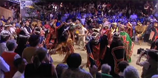A group of dancers move in circles around the dirt floor at the center of the big house, they are surrounded by audience.