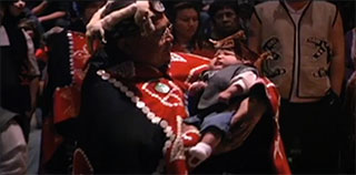 A Kwakwaka'wakw women in ceremonial regalia is cradling a baby who also is dressed in ceremonial regalia.