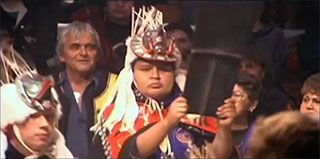 A young Kwakwaka'wakw man dressed in ceremonial regalia holding aloft a copper, behind him stands Chief Cranmer.