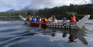 A large Kwakwaka'wakw canoe is moving diagonally across the screen over calm waters against a forested and mountainous background.