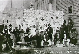 A group of Kwakwaka'wakw men are standing or seated in front of a large stack of flour sacks and boxes that have been gathered to present at a potlatch.