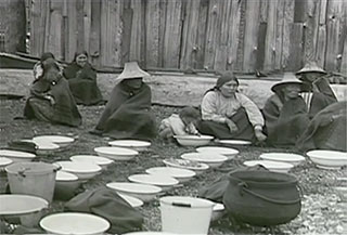 Kwakwaka'wakw women in traditional dress sit on the ground next to food containers used in preparing food for a potlatch