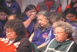 A group of Kwakwaka'wakw taking part in a mourning ceremony during a Potlatch, front row of elders in button blankets.