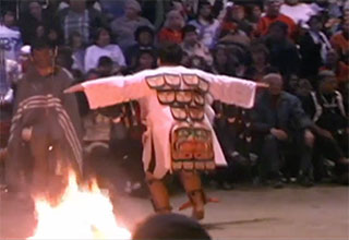 The back of a dancer wearing an embroidered tunic next to a fire pit in the big house.