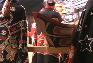 Potlach celebrants in regalia carry a large carved cedar container of eulachon oil into the big house.
