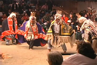 A group of dancers perform in woven ceremonial regalia to the right of a fire pit in the big house.