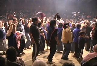 A group of people move in circles around the dirt floor at the center of the big house, they are surrounded by a large audience.