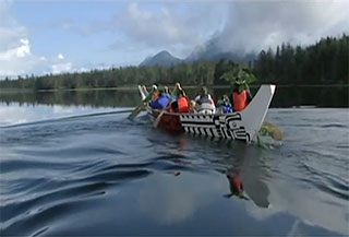 Image alt tag: A large Kwakwaka'wakw canoe is moving diagonally across the screen over calm waters against a forested and mountainous background.