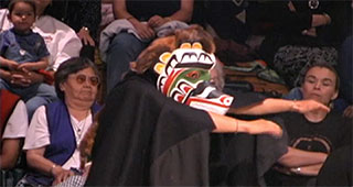 A potlatch dancer wears a ceremonial mask and black cape, his arms stretch to the right. Behind him sit a number of people.