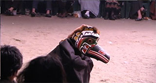 A potlatch dancer wearing a bird mask and black cape crouches and hops along the dirt floor of the big house.