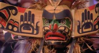 Close-up view of a transformation mask, carved from cedar and brightly decorated, shown in the open position.