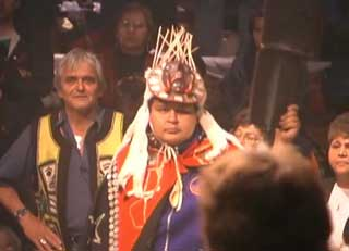 Image of a Kwakwaka'wakw dancer at a potlatch wearing ceremonial regalia consisting of a button blanket, carved and decorated frontlet.