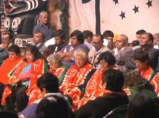 Image shows a group of Kwakwaka'wakw taking part in a mourning ceremony during a Potlatch, front row of elders in button blankets.