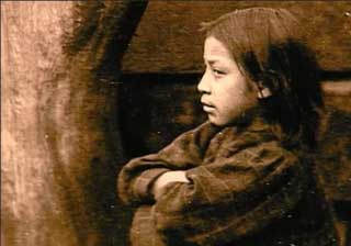 Historical sepia-tone photo by Edward S. Curtis shows a Kwakwaka'wakw youth in profile.