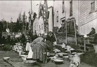 Historical black and white photograph showing a group of Kwakwaka'wakw adults standing among gifts gathered in preparation for a potlatch in Alert Bay.