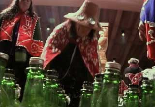Image shows a figure wearing a woven cedar hat and button blanket regalia before a group of bottles which have been filled with oolichan oil.